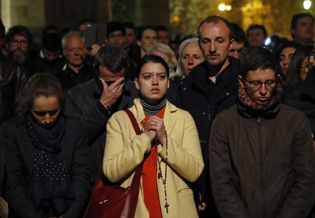 燃える大聖堂を祈りながら見上げる市民ら=15日、パリ(AP)