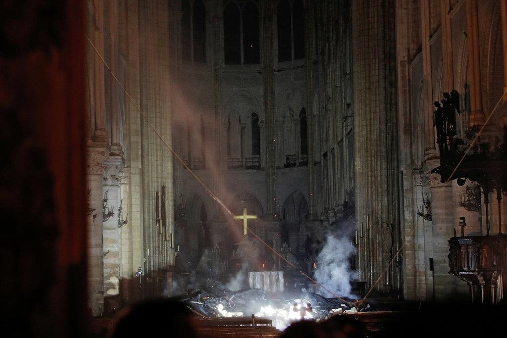煙が立ちこめるノートルダム大聖堂の内部=16日、パリ(ロイター)