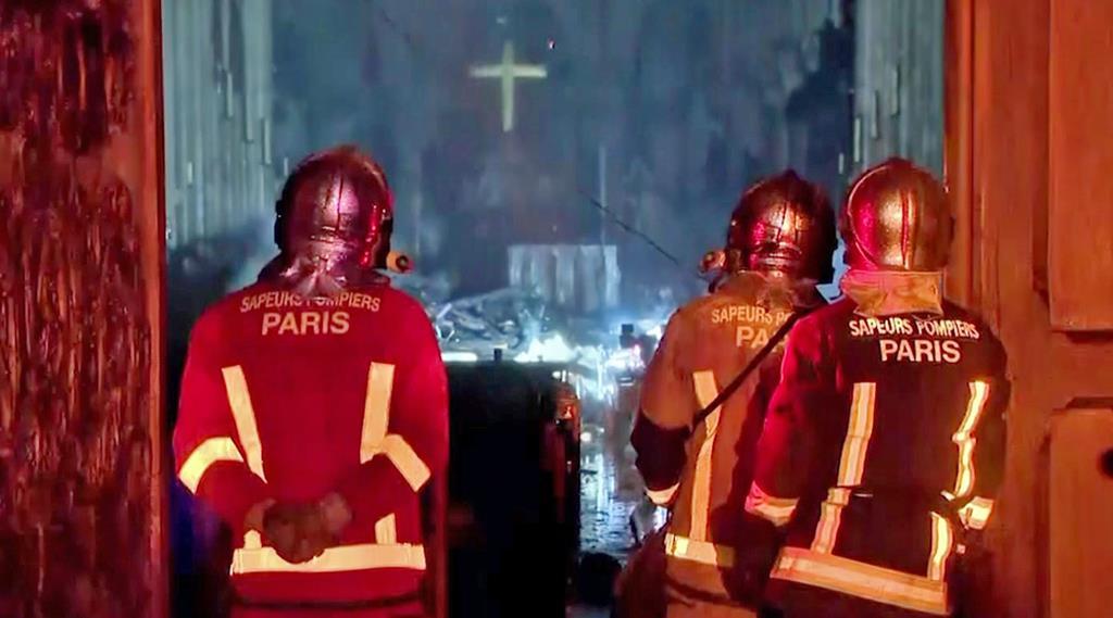 大規模な火災が発生したノートルダム寺院の入り口で立ち尽くす消防士たち=15日、パリ(AP)