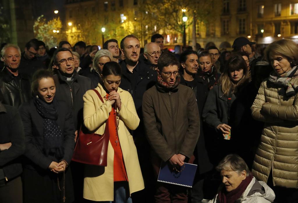 燃えるノートルダム大聖堂に向かい祈る人々=15日、パリ(ロイター)
