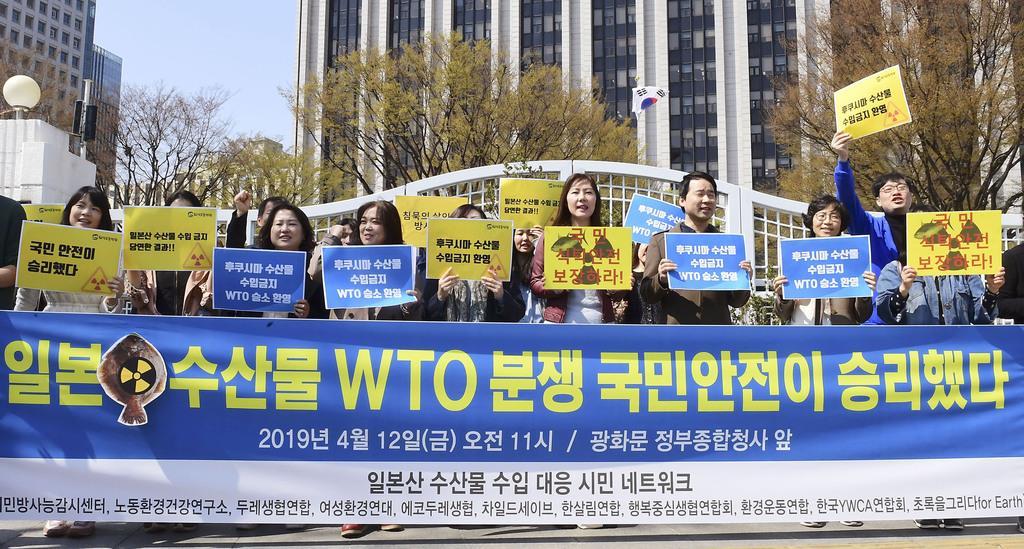 12日、水産物輸入禁止措置を巡り、WTOで韓国勝訴の判断が出たことを喜ぶ市民団体=ソウル(共同)
