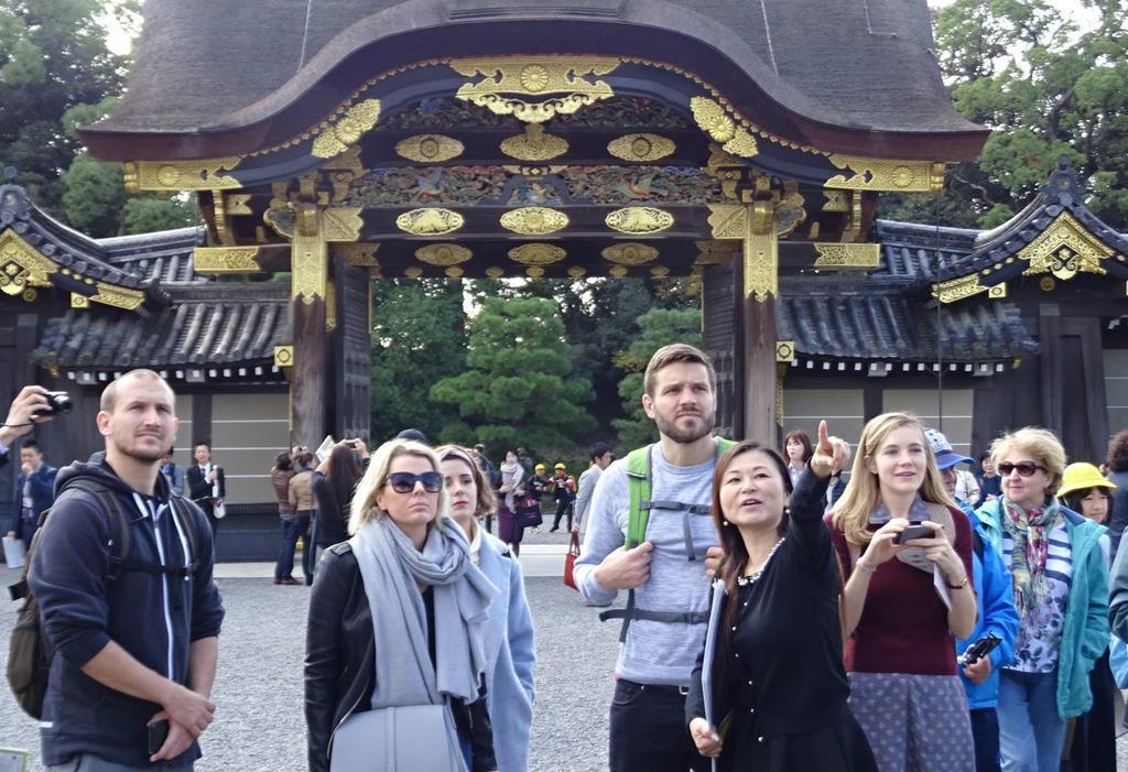 女性ガイドから英語で二条城の案内を受ける外国人観光客=京都市中京区