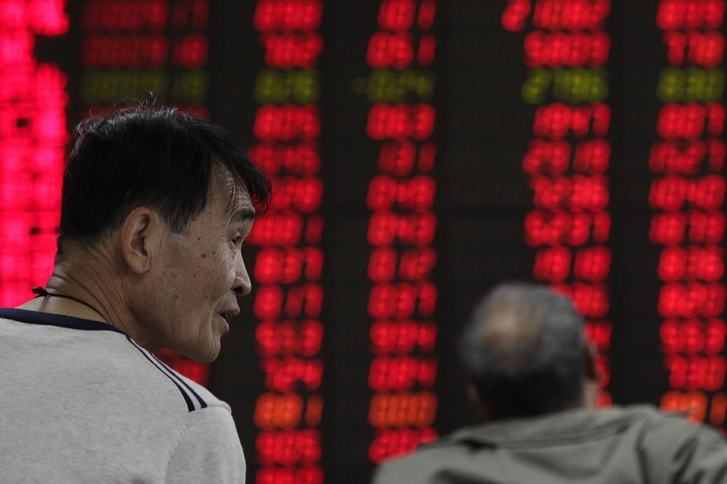 北京の証券会社で株価ボードを見る投資家。中国株は年初から上昇基調を維持している=8日(AP)