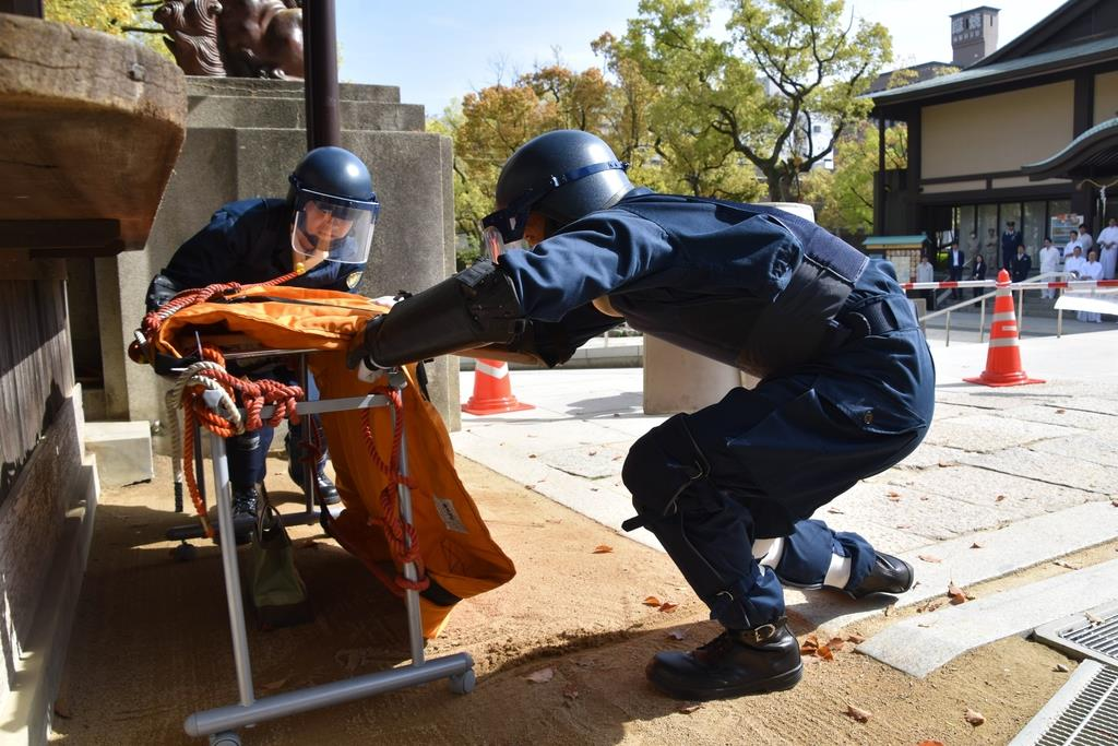 神社内に放置された爆発物に防爆マットをかける警察官=神戸市中央区(林信登撮影)