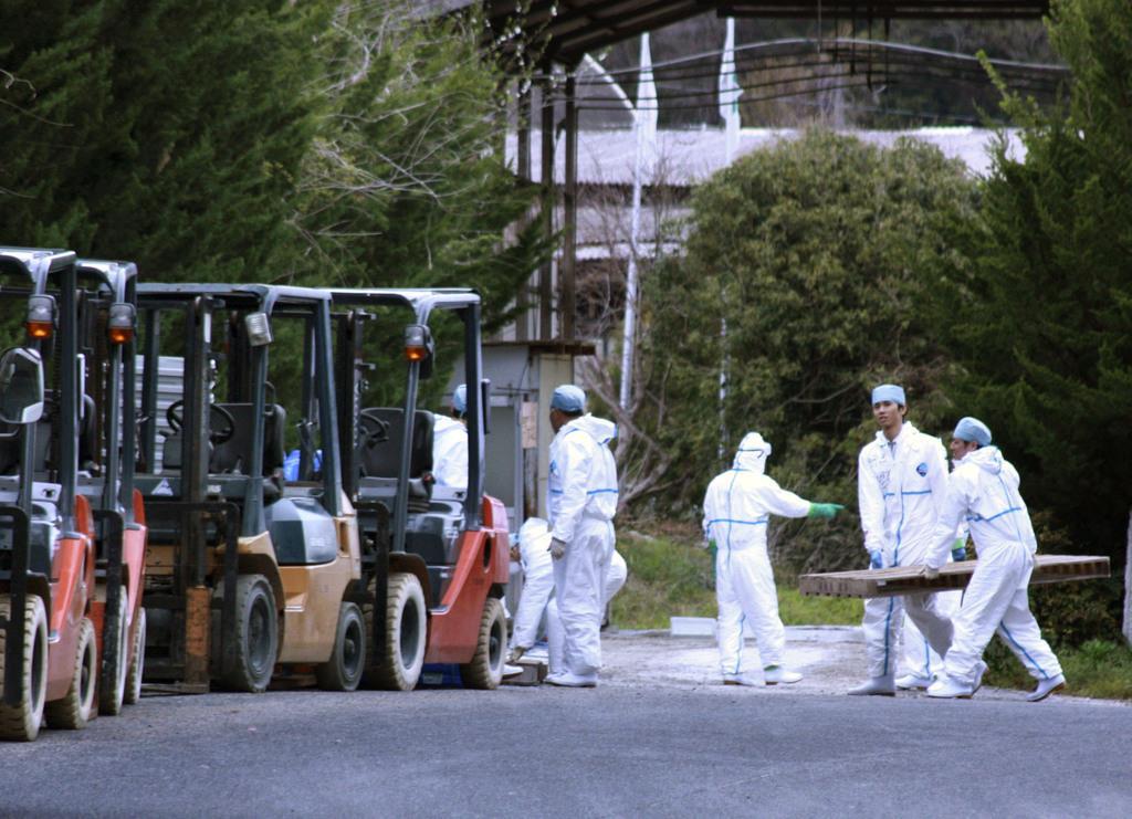 豚コレラが発生した岐阜県恵那市の養豚場近くで防疫作業などの準備をする作業員=17日午後