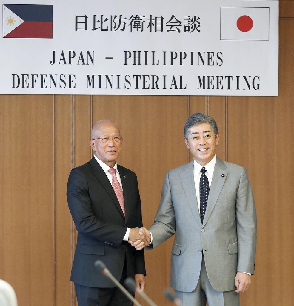会談を前にフィリピンのロレンザーナ国防相(左)と握手する岩屋防衛相=17日午後、防衛省
