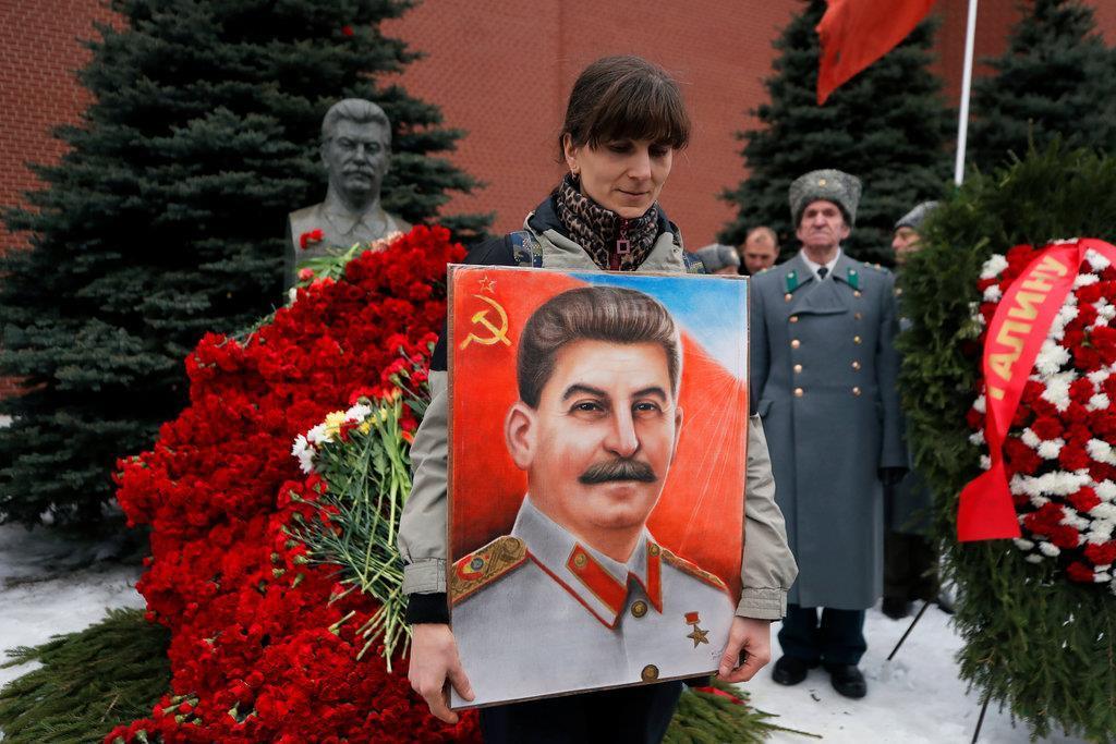死去66年を記念したセレモニーで、スターリンの肖像画を抱える女性=3月5日、モスクワ・赤の広場(ロイター)