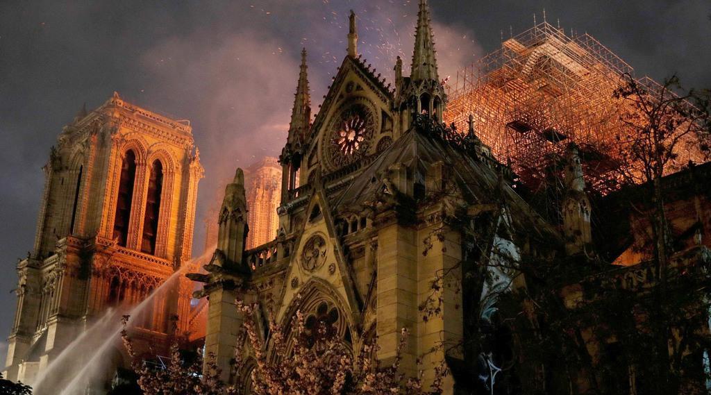 大規模な火災で暗くなっても消火活動が続くノートルダム寺院