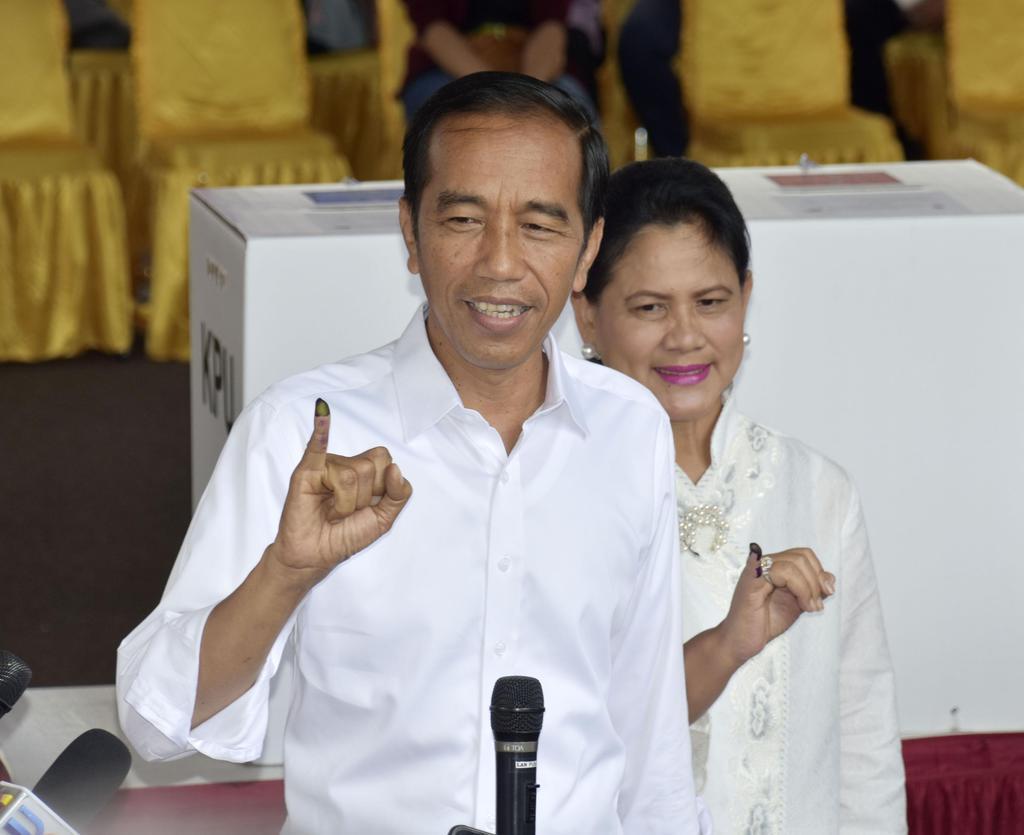 17日、インドネシアの首都ジャカルタで投票を終え、投票済みの目印となるインクが付いた指を見せるジョコ大統領(左)と夫人(共同)