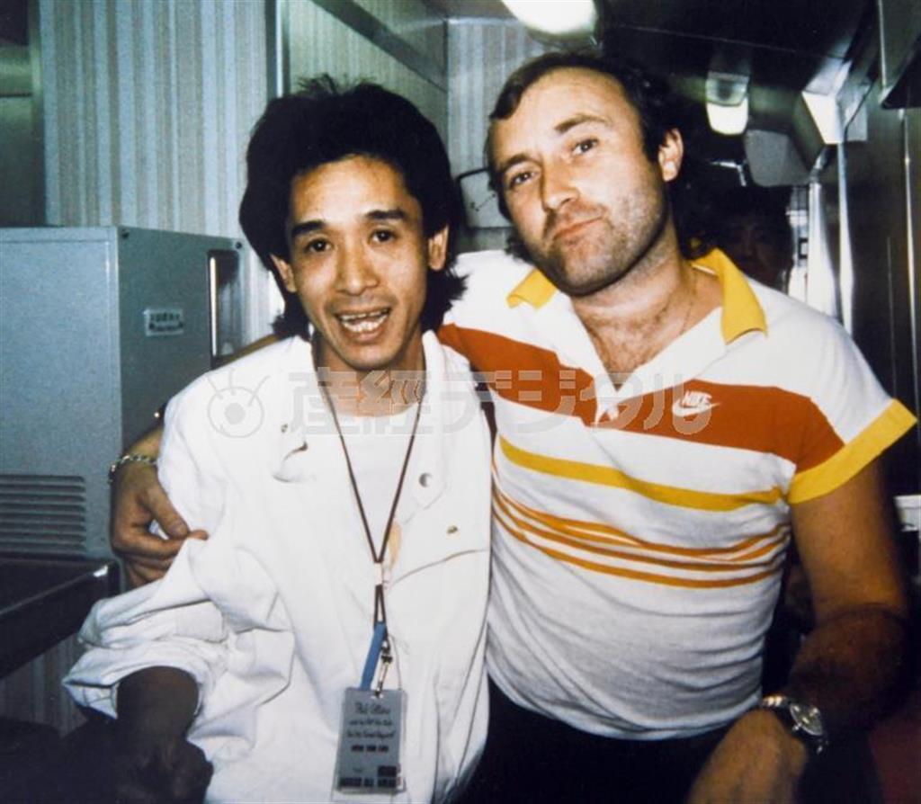 イギリスのロックスター、フィル・コリンズと写真に納まる高橋さん(高橋さん提供)