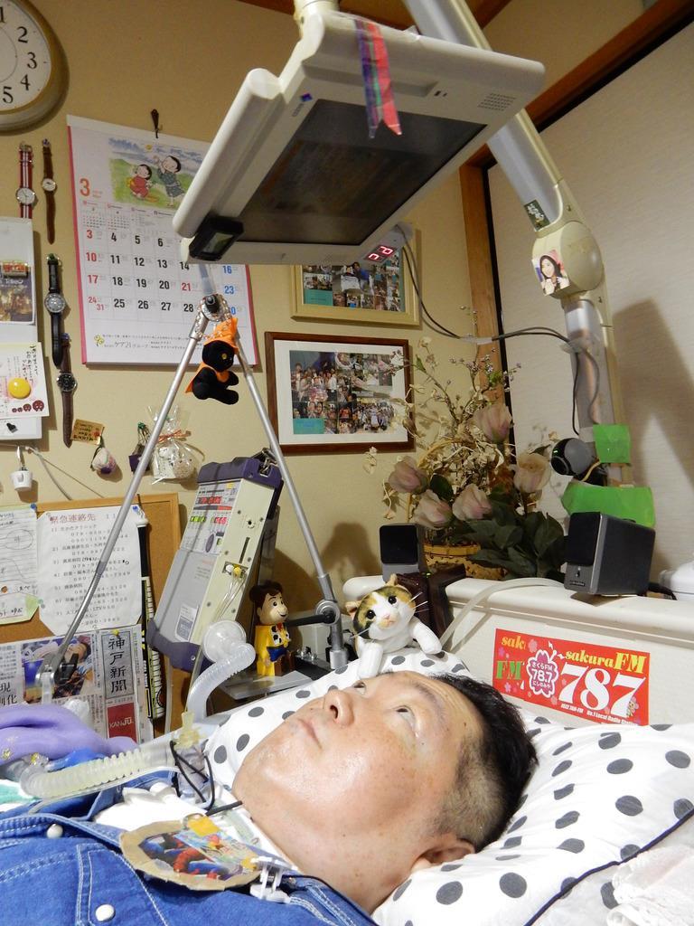 パソコンのモニターを見る蔭山武史さん。黒い針金のような形のマウスをあごに当てて操作している=神戸市北区