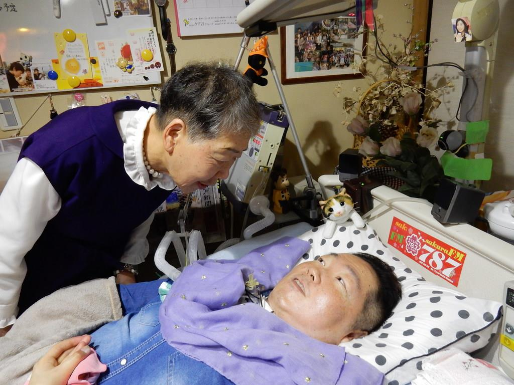 母の節子さんに話しかけられ、笑顔を見せる蔭山武史さん=神戸市北区