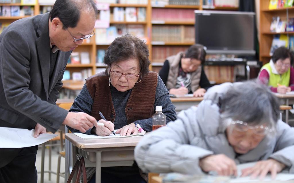 「夜間中学で人生を取り戻した」と話す村上玉子さん(左から2人目)。今も識字教室で学び続ける=神戸市の湊川高校内(安元雄太撮影)