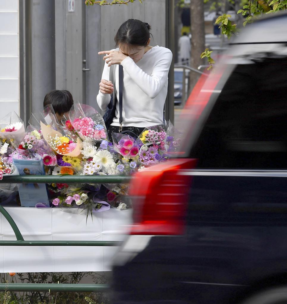 乗用車が暴走し、母子が死亡した事故現場付近で涙をぬぐう女性=20日午後、東京都豊島区