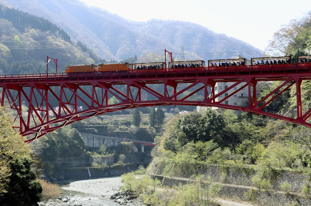 一部区間で運転を再開し、鉄橋を渡る黒部峡谷鉄道のトロッコ電車=20日午前、富山県黒部市