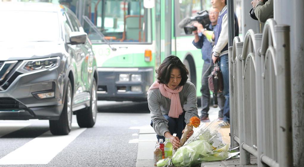 事故現場の横断歩道で花を供える女性=22日午前8時19分、神戸市中央区(彦野公太朗撮影)