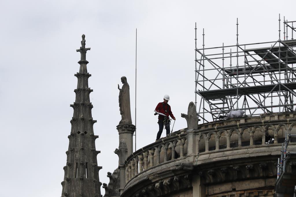 火災にあったノートルダム寺院で、防水などのための作業を行う作業員=24日、パリ(AP)