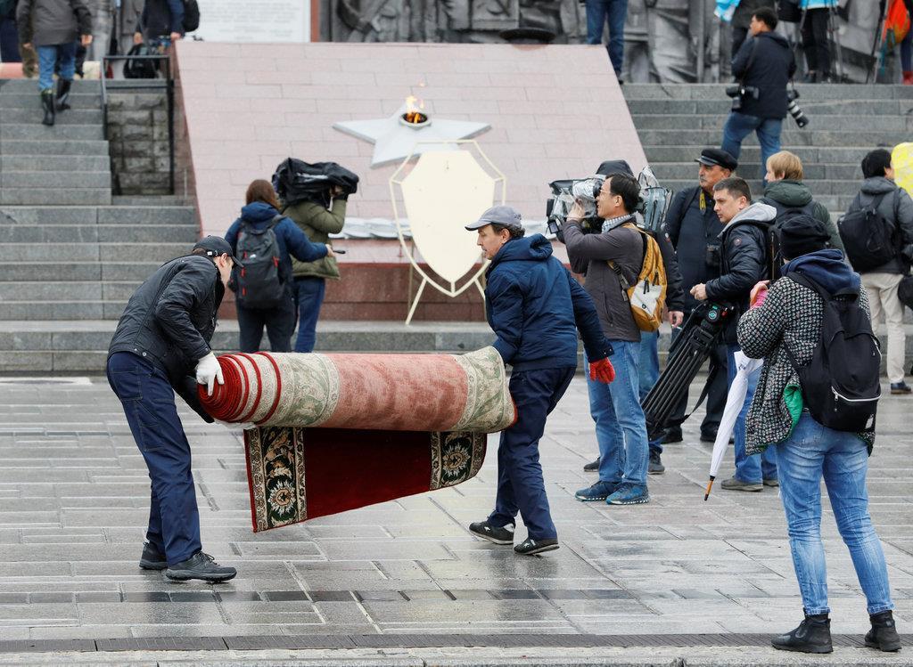 金正恩氏の献花取りやめで絨毯を撤去する作業者ら=26日、ウラジオストク(ロイター)