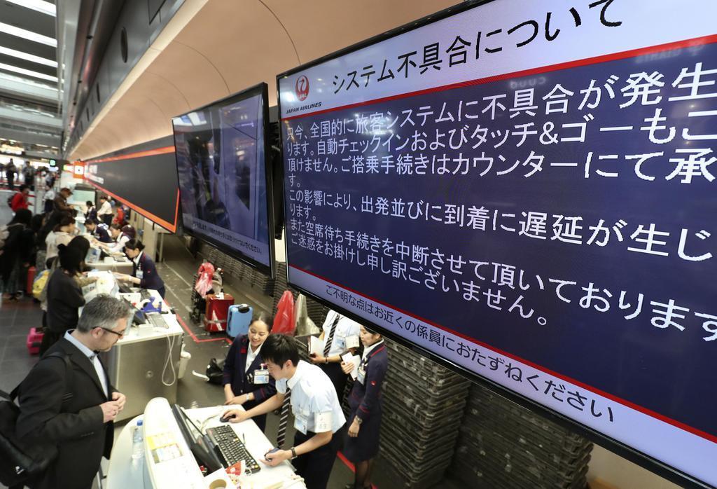 日航の旅客システムに不具合が発生したことを伝えるモニター=8日午前8時32分、羽田空港