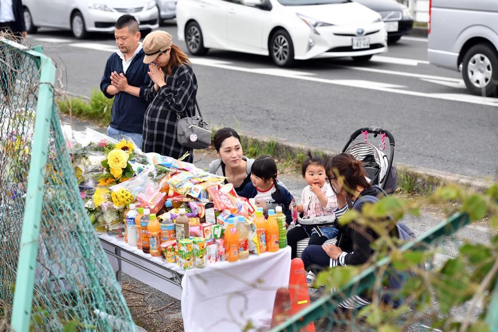 事故現場に設置された献花台を訪れ、手を合わせる親子連れら=9日午前、大津市(永田直也撮影)