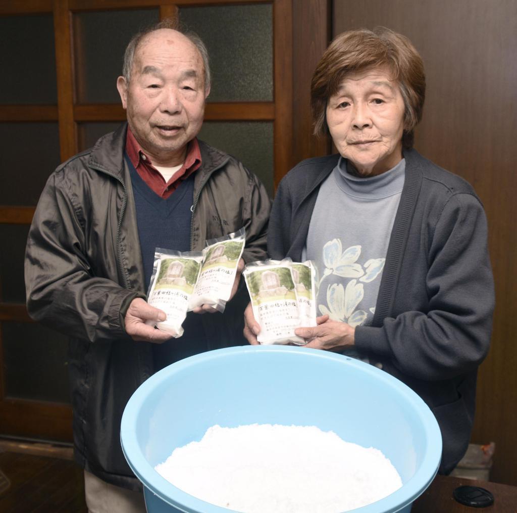 手作りの塩を手にする橋野三郎さん、世津子さん夫婦=福井県敦賀市