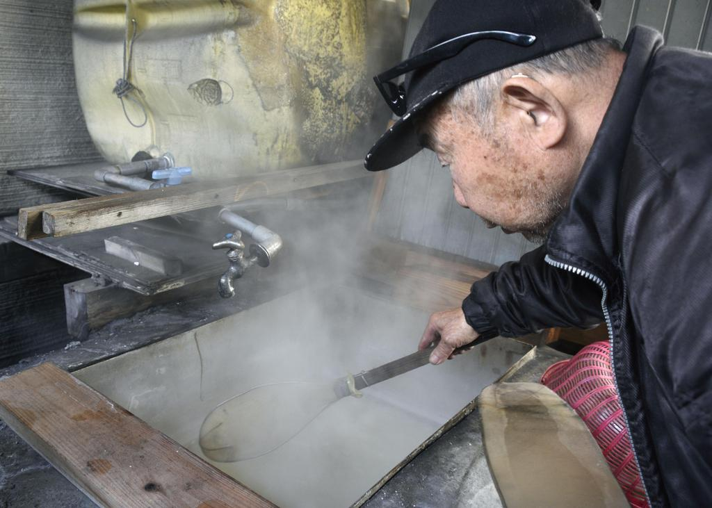 塩作りのため、釜に入れた海水をかき混ぜる橋野三郎さん=福井県敦賀市