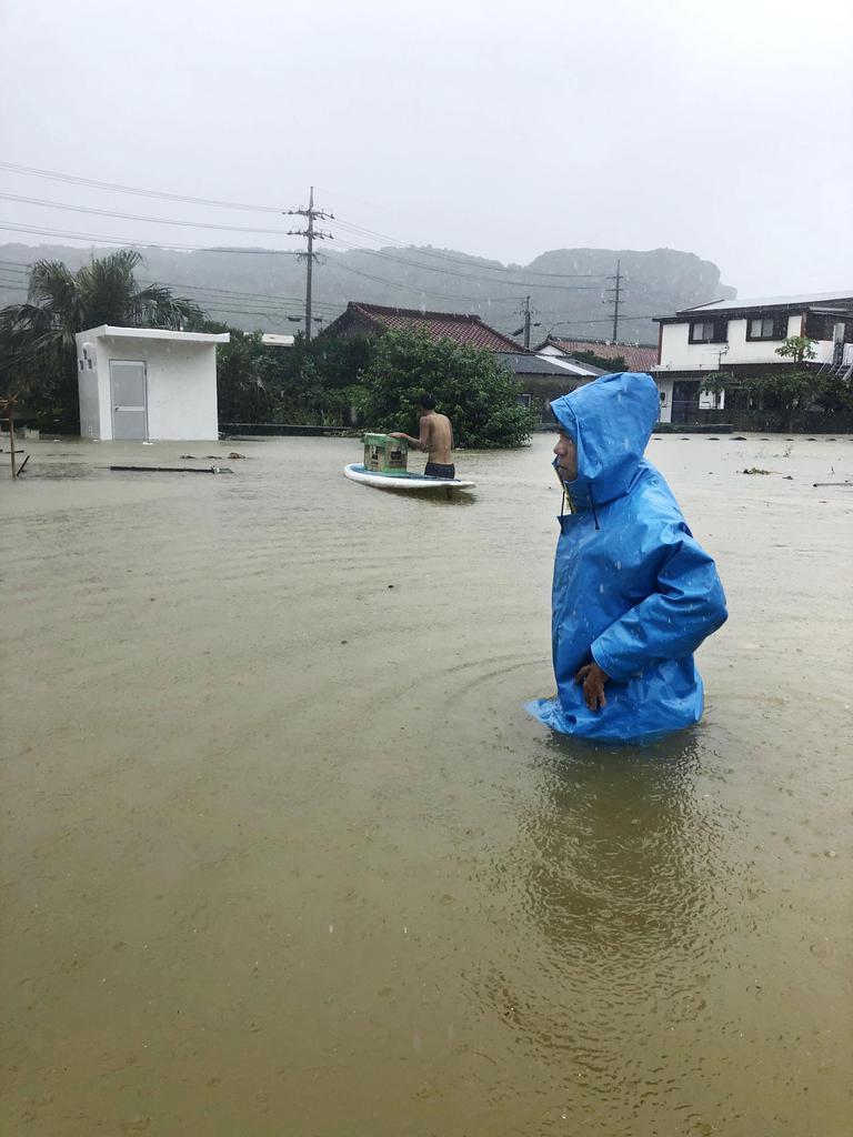 大雨の影響で冠水した沖縄県与那国町祖納の道路を歩く人=13日午前(与那国町の住民提供)