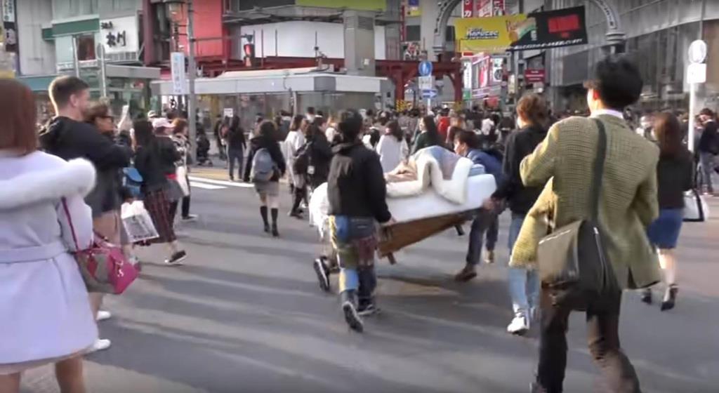 東京・渋谷のスクランブル交差点内に、男性が寝そべった状態のベッドを置く動画(ユーチューブから)