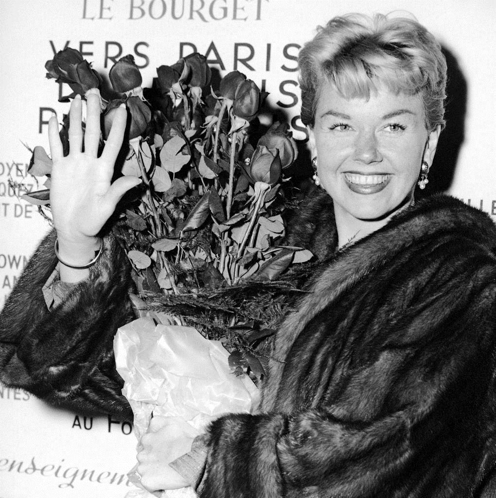 パリの空港でバラの花束を持つドリス・デイさん=1955年(AP=共同)