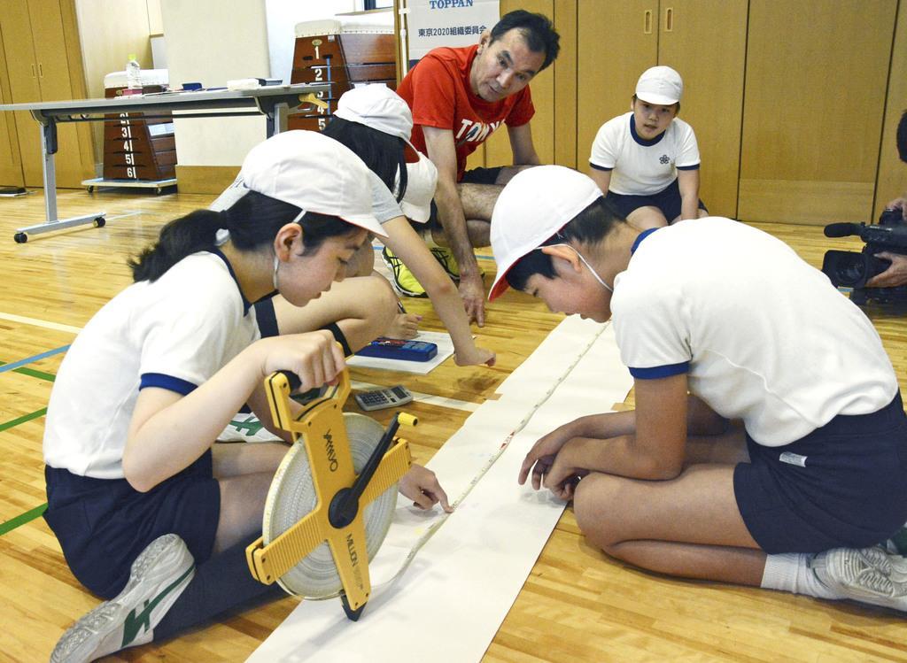 垂直跳びした後に高さを測る児童とバレーボール元日本代表の大竹秀之さん(奥左)=13日、東京都中央区