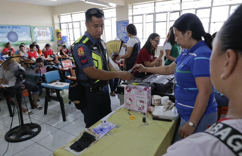 中間選挙で票を投じる警察官。ドゥテルテ大統領派が優勢の見通し=13日、マニラ(AP)