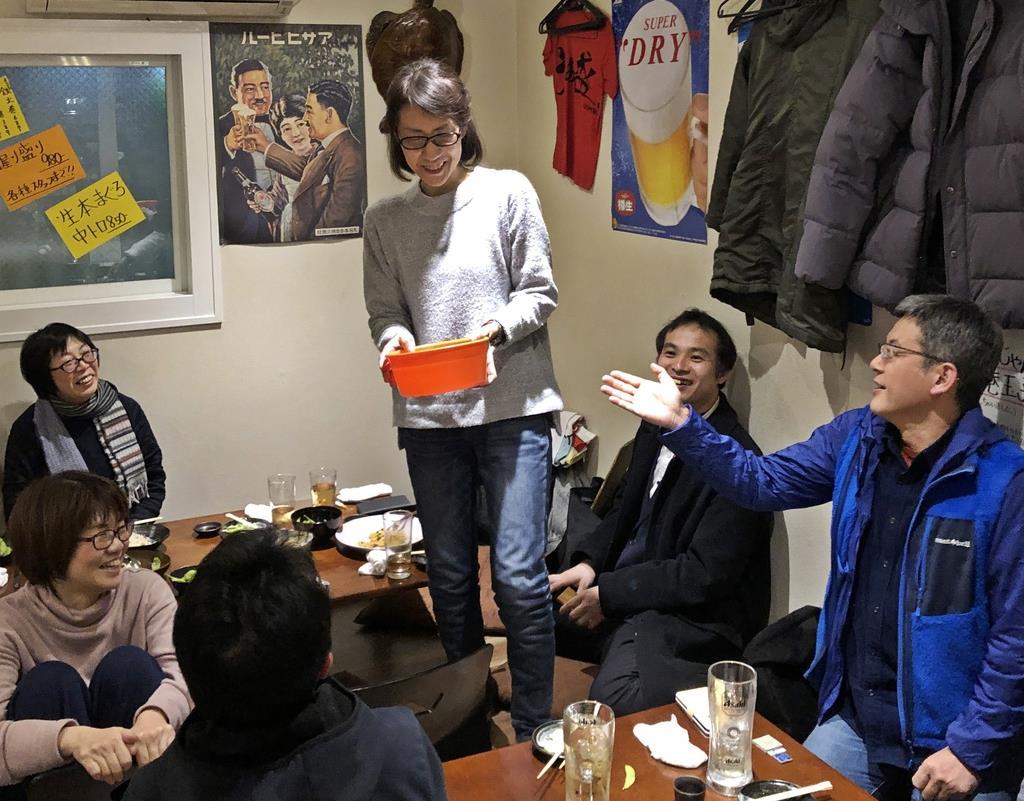銭湯の桶を持つ女将の堀江寿美さんを囲み、和やかなムードの中で行われたお別れ会=大阪市城東区