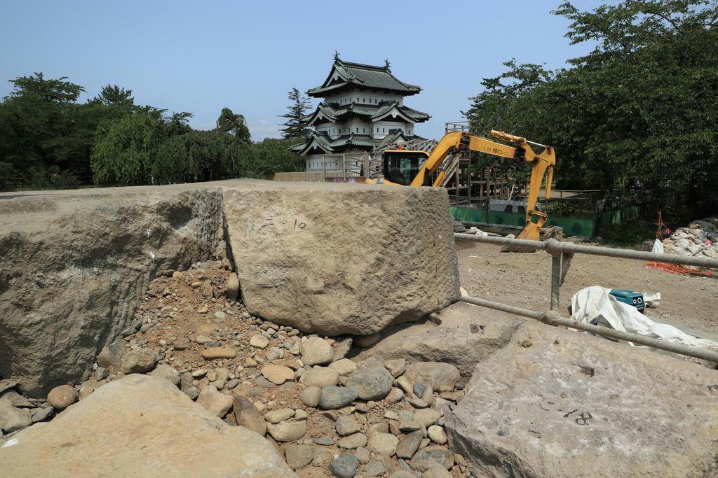 修復のため、解体される天守台の石垣。奥に見えるのは「曳屋」によって本丸中心部に移された天守 (いずれも筆者撮影)