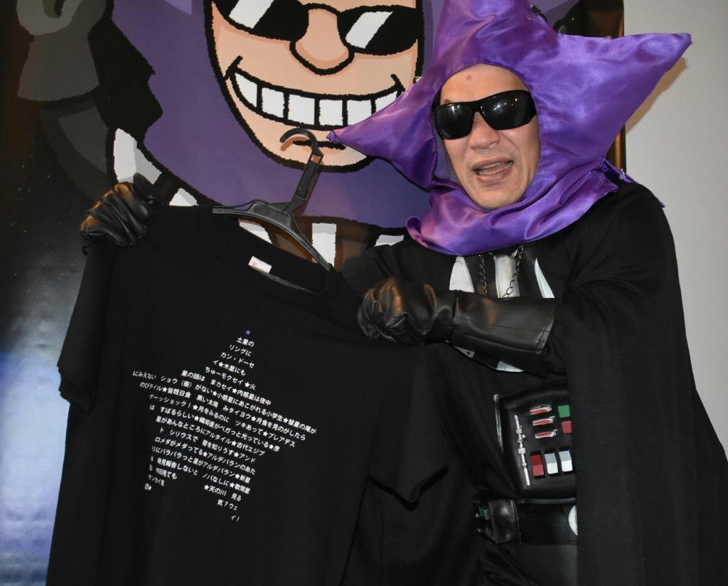 ダジャレがぎっしりと書かれたTシャツをアピールするブラック星博士=明石市人丸町