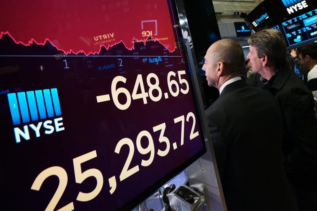 大幅に下落した株価を見る投資家ら=13日、ニューヨーク証券取引所(AP)