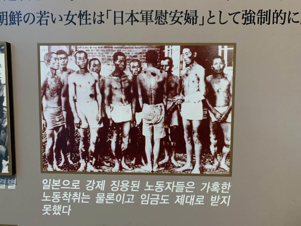 釜山近代歴史館に展示されている朝鮮人徴用工とは無関係の写真。「日本に強制徴用された労働者」との説明がある(名村隆寛撮影)