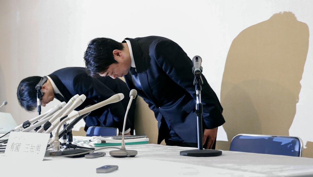 記者会見の冒頭、一礼するスルガ銀行の有国三知男社長(右)=15日午後、静岡県沼津市