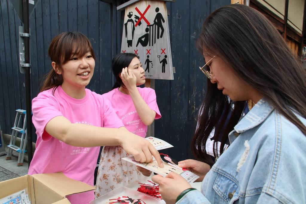 オリジナルのしおりとステッカーを配る京都女子大の学生ら=京都市東山区