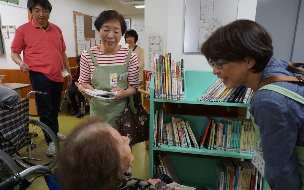 図書館が高齢者施設を巡回するサービスも。入所者が図書館ボランティアと一緒に楽しそうに本を選ぶ=大阪市天王寺区の介護老人保健施設「れいんぼう夕陽丘」