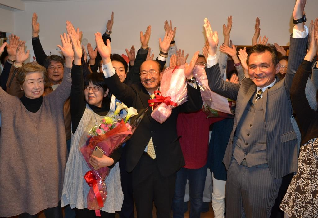 大阪府豊能町選で初当選を決め、バンザイして喜ぶ塩川恒敏氏(中央)=3月3日夜、同町