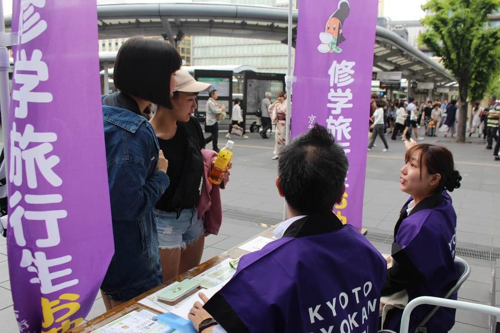 修学旅行生の質問に応じる「お助けマン」(右)=京都市下京区