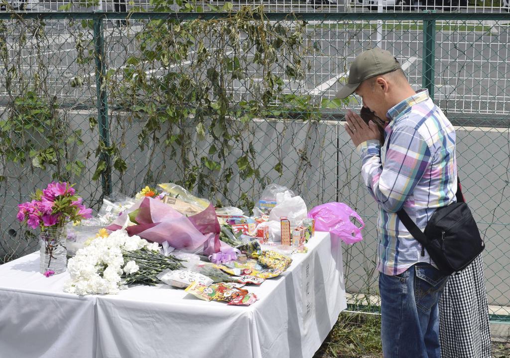 保育園児が死傷した事故から1週間となり、現場近くの献花台の前で手を合わせる人たち=15日午前、大津市
