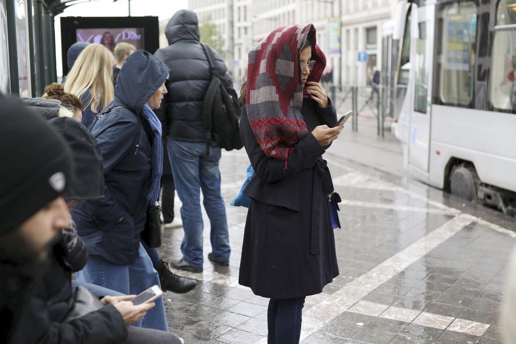 ブリュッセルで携帯電話を見る女性=9日(ロイター=共同)