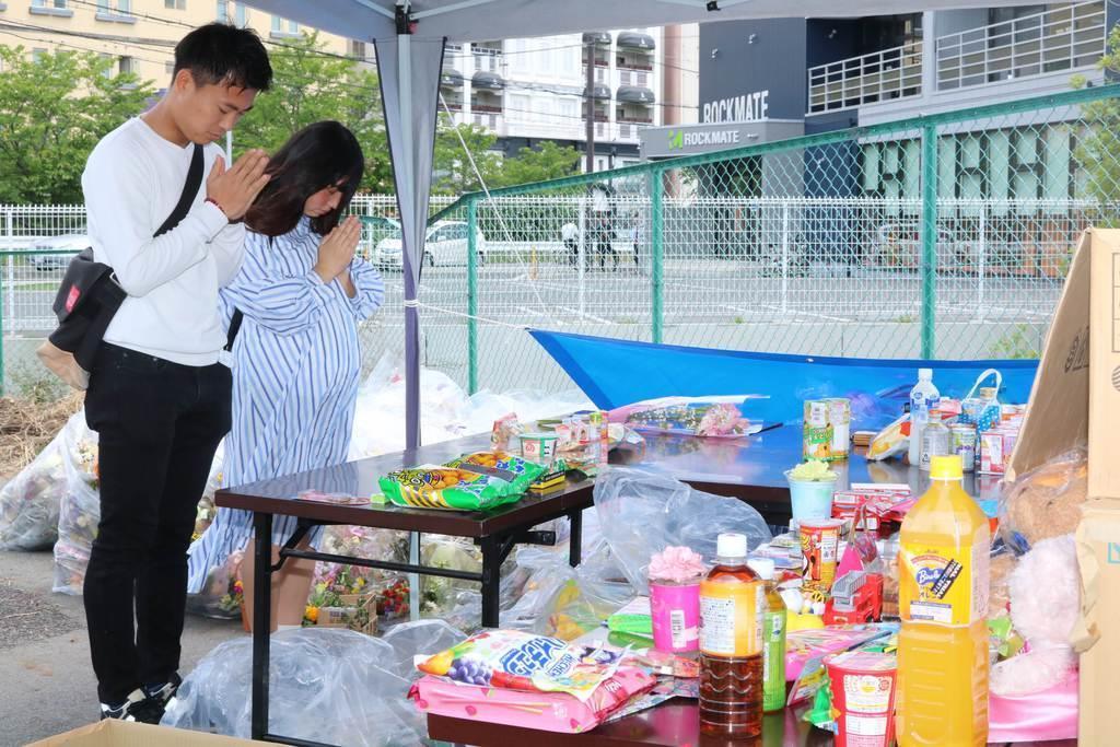 大津市の保育園児死傷事故現場近くに設けられた台で手を合わせる人=15日