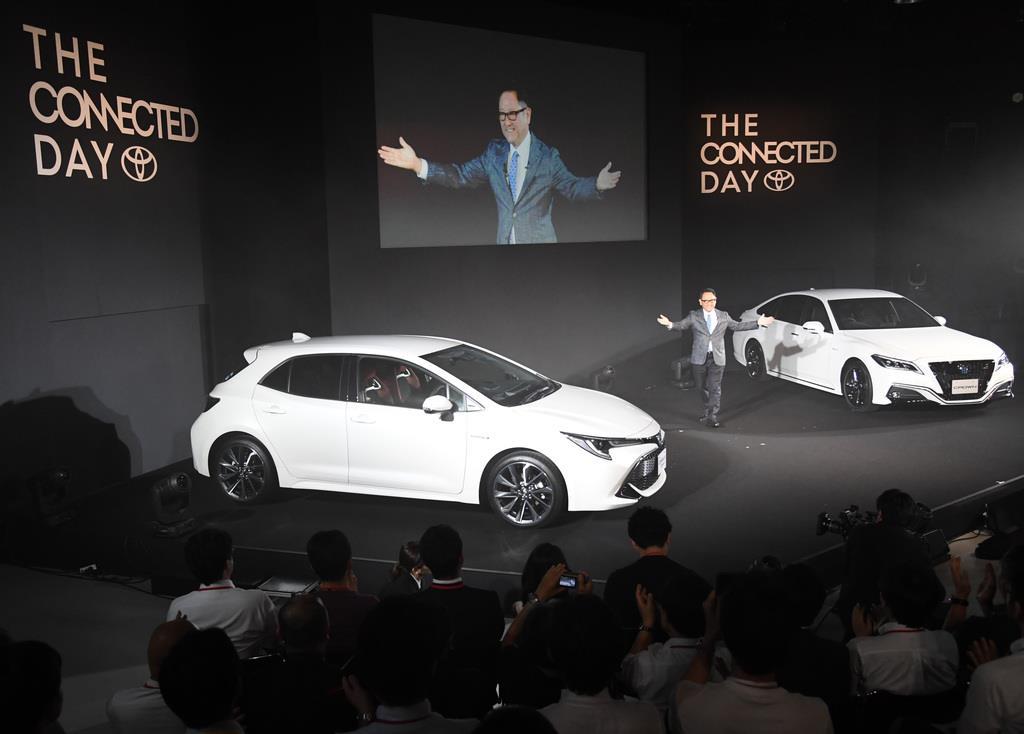 「カローラスポーツ」(左手前)と「クラウン」の両新型車を発表するトヨタ自動車の豊田章男社長。トヨタを象徴する多くの車種にはすでにハイブリッド車モデルが設定されている=2018年6月、東京都江東区(宮川浩和撮影)