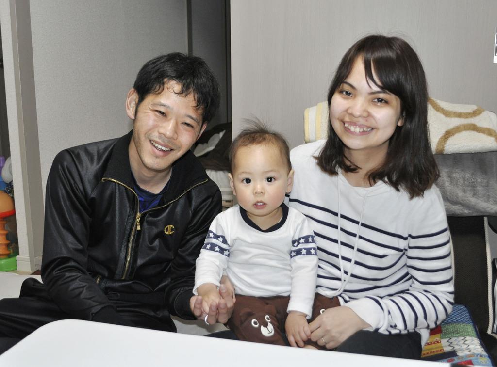 長男の陽飛ちゃんを抱く小林聡恵さん(右)と夫の守さん=4月、茅ケ崎市