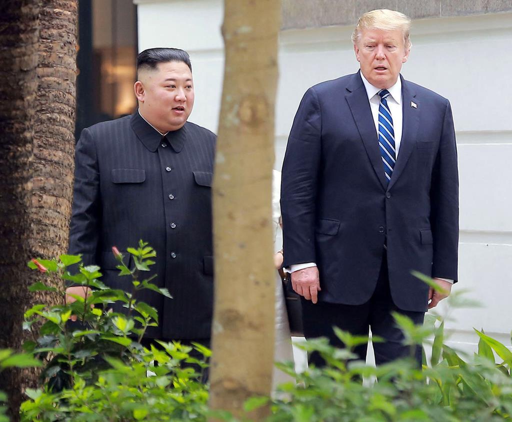 2月、会談場のホテルの中庭を歩くトランプ米大統領(右)と北朝鮮の金正恩朝鮮労働党委員長=ハノイ(朝鮮中央通信=共同)