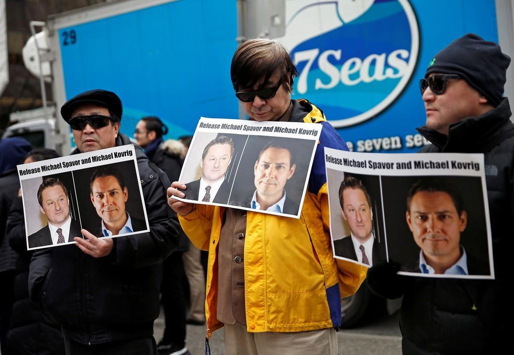 カナダの元外交官、マイケル・コブリグ氏らの解放を中国に求め、ファーウェイ幹部を聴聞中の裁判所前でプラカードを掲げる人たち=3月、カナダ・バンクーバー(ロイター)