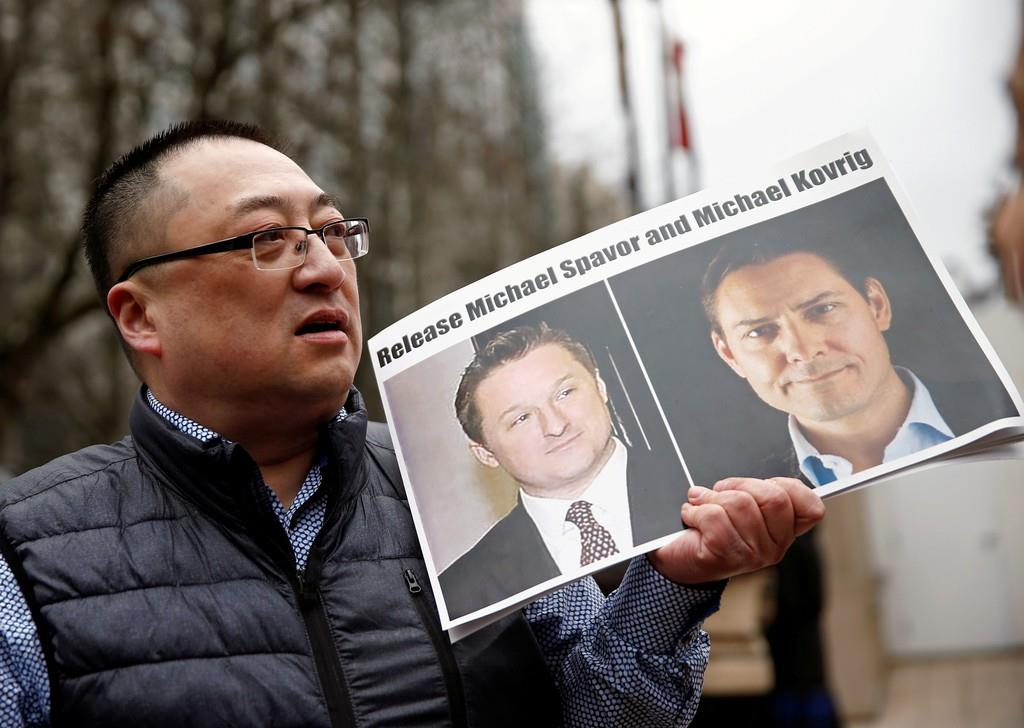 カナダの元外交官、マイケル・コブリグ氏らの解放を求め、ファーウェイ幹部を聴聞中の裁判所前でプラカードを掲げる市民=3月、カナダ・バンクーバー(ロイター)