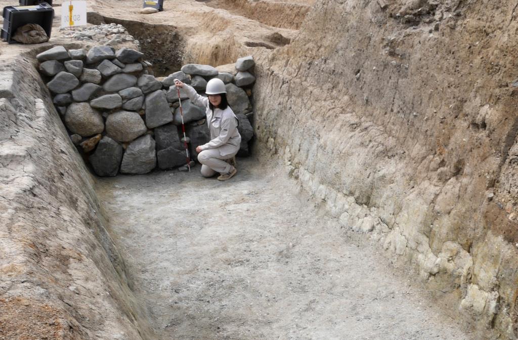 六波羅からから出土した平家が防御用に築いたとみられる堀と、平清盛時代に築かれた石垣=16日午後2時31分、京都市東山区